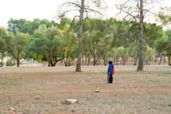 Kleiner Junge ganz, der allein einen Rucksack im Wald trägt Lizenzfreies Stockfoto