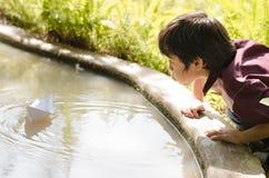 Kleiner Junge genießen, Papierboot durchzubrennen Lizenzfreie Stockbilder