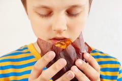Kleiner Junge genießt ein appetitanregendes Muffin auf weißem Hintergrundabschluß oben lizenzfreie stockfotos