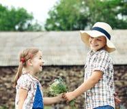 Kleiner Junge gibt dem kleinen Mädchen Blumen Stockfoto