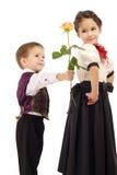 Kleiner Junge gibt ein Mädchen, das ein Gelbes stieg Stockfotografie