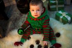 Kleiner Junge hält Weihnachtsball in der Hand, sitzt und spielt durch Kiefer lizenzfreie stockfotos