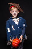 Kleiner Junge in Halloween-Kostüm des Piraten aufwerfend mit Kürbis über schwarzem Hintergrund stockfotografie