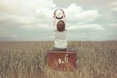 Kleiner Junge hebt in den Himmel eine Uhr in einer surrealen Landschaft an Stockfoto