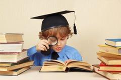 Kleiner Junge im akademischen Hut studiert alte Bücher mit Vergrößerungsglas Stockbild