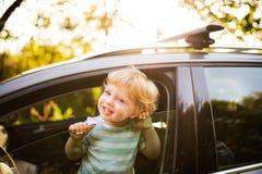 Kleiner Junge im Auto, schauend aus Fenster heraus Stockfotografie