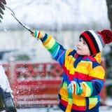 Kleiner Junge im bunten Winter kleidet das Spielen mit Schneemann, heraus Stockbild