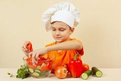 Kleiner Junge im Chefhut setzt gehacktes Gemüse für Salat in eine Schüssel ein Stockbild