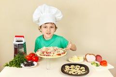 Kleiner Junge im Chefhut zeigt, wie man Pizza kocht Stockfotografie