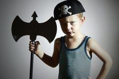 Kleiner Junge im Karnevalskostüm Verärgerter Krieger Kinder in der erwachsenen Kleidung maskerade Junger Junge gekleidet als Pira lizenzfreie stockfotos