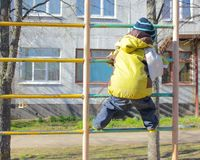 Kleiner Junge, im Kindergarten, auf dem Spielplatz, klettert auf dem Schalter Lizenzfreie Stockfotos