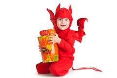 Kleiner Junge im Kostüm des roten Teufels, das nahe großem Eimer sitzt Lizenzfreies Stockbild