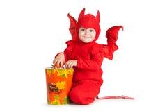 Kleiner Junge im Kostüm des roten Teufels, das nahe großem Eimer sitzt Stockfotografie