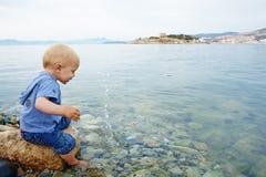 Kleiner Junge im Meer Stockbilder