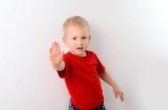 Kleiner Junge im roten Hemd, das Stoppschild zeigt Stockfotos