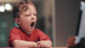 Kleiner Junge im roten Hemd, das vor Tablette und Gegähne sitzt stock video