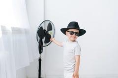 Kleiner Junge im schwarzen Hut und in der Sonnenbrille, die vor Ventilator abkühlt Lizenzfreies Stockfoto