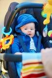 Kleiner Junge im Spaziergänger, der mit Spielwaren spielt Stockbild
