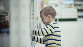 Kleiner Junge im Supermarkt wählen eine Flasche Mineralwasser stockbild