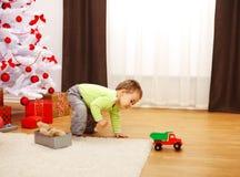 Kleiner Junge im Weihnachten, spielend mit neuem Spielzeugauto Stockbild