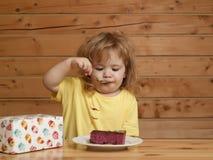 Kleiner Junge isst Fruchtkuchen Stockbild