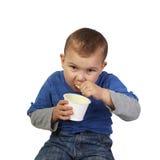 Kleiner Junge isst Jogurt Lizenzfreies Stockfoto
