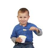 Kleiner Junge isst Jogurt Stockfoto