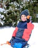 Kleiner Junge isst Tangerine und krächzt Lizenzfreie Stockfotografie