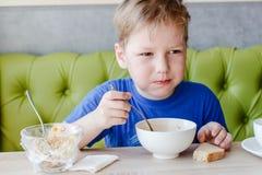 Kleiner Junge ist appetitanregend, eine köstliche Suppe mit einem großen Löffel essend lizenzfreie stockfotos
