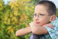 Kleiner Junge ist mageres Winkelstück auf Brückenzaun stockfotos