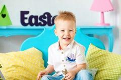 Kleiner Junge 2-3 Jahre blonde Haar, die auf dem Boden und dem Lachen sitzen Lizenzfreies Stockfoto