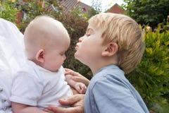 Kleiner Junge küßt seine Schätzchenschwester Stockbilder