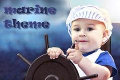 Kleiner Junge kleidete oben als Seemann an, der das Lenkrad hält stockfoto