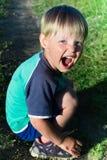 Kleiner Junge kurz gesagt sitzend auf Gras Stockfoto