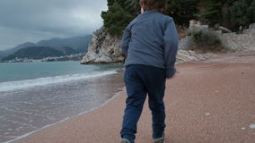 Kleiner Junge läuft schnell allein entlang sandige Seeküste der Bucht stock video