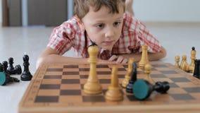 Kleiner Junge liegt auf dem Boden und spielt Schach stock footage