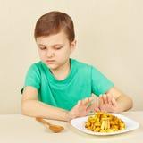 Kleiner Junge möchte nicht gebratene Kartoffeln essen lizenzfreie stockbilder