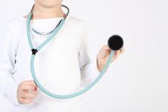 Kleiner Junge mögen Doktor mit einem Stethoskop in den Händen Stockbild