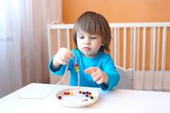 Kleiner Junge machte mehrfarbige Perlen Lizenzfreie Stockfotografie