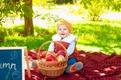 Kleiner Junge mit Apfel im Herbst Stockfoto