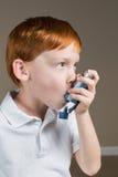 Kleiner Junge mit Asthma unter Verwendung seines Inhalators lizenzfreies stockbild