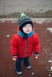 Kleiner Junge mit blauen Augen auf einem Winterweg lizenzfreies stockbild