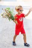 Kleiner Junge mit Blumen Stockfotos