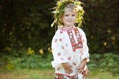 Kleiner Junge mit Blumenkranz Stockbild