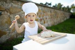 Kleiner Junge mit dem Chefhutkochen Stockfotos