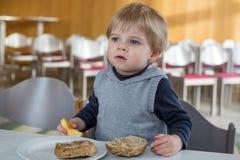 Kleiner Junge mit dem Essen des Brotes und des Apfels im Kindergarten stockbild