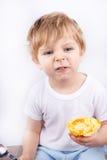 Kleiner Junge mit dem Essen des Käsekuchenmuffins. Stockbilder