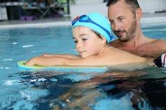 Kleiner Junge mit dem Monitor, der wie man lernt, schwimmt Lizenzfreie Stockbilder