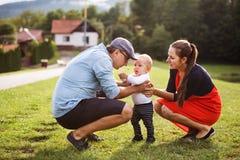 Kleiner Junge mit den Eltern, die erste Schritte machen lizenzfreie stockfotografie