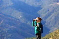 Kleiner Junge mit den Ferngläsern, die in den Bergen wandern Stockfotografie